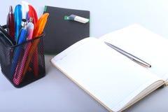 Bunte Notizbücher und Büroartikel auf weißer Tabelle Lizenzfreie Stockfotografie