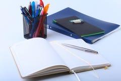 Bunte Notizbücher und Büroartikel auf weißer Tabelle Stockbild