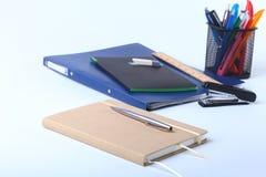 Bunte Notizbücher und Büroartikel auf weißer Tabelle Lizenzfreies Stockbild