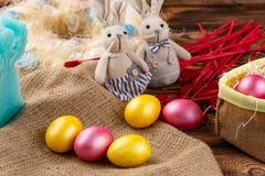 Bunte Osterei- und Kaninchenpuppe auf hölzernem Hintergrund lizenzfreie stockfotografie