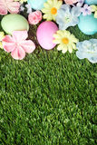 Bunte Ostereier auf Gras mit Blumen Stockbild