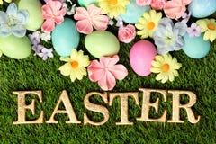 Bunte Ostereier auf Gras mit Blumen Lizenzfreie Stockfotos