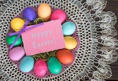 Bunte Ostereier auf Platte mit glücklicher Ostern-Karte im Weinlese-Stillleben mit Spitze-Tischdecke Stockbild