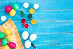 Bunte Ostereier, Bürste und Farbe auf Hintergrund des hölzernen Brettes mit Raum Lizenzfreie Stockbilder