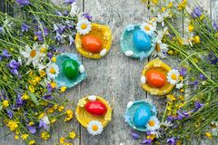 Bunte Ostereier, die auf den Flechtweidenplatten in Form eines Nestes auf hölzernem Hintergrund mit einem Blumenstrauß von wildem Stockbild
