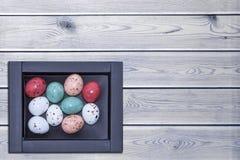 Bunte Ostereier in einem braunen Kasten auf einem weißen Holztisch, Ostern-Konzept mit Raum für Text Beschneidungspfad eingeschlo Stockfotografie