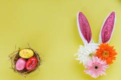 Bunte Ostereier in einem Nest und in einer Osterhasen-Ohrkaninchendekoration mit Gerbera- und Chrysanthemenblumen lizenzfreie stockfotos