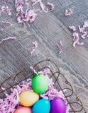 Bunte Ostereier im Korb, gegen einen Holzfußboden-Hintergrund Stockfotografie