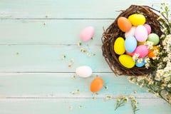 Bunte Ostereier im Nest mit Blume auf rustikalem hölzernem Plankenhintergrund in der blauen Farbe Jahreszeit des Feiertags im Frü lizenzfreie stockbilder