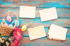 Bunte Ostereier im Nest mit Blume und leeren altes Papierfotoalbum auf hölzerner Tabelle Stockfoto