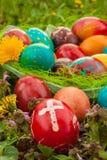 Bunte Ostereier mit Blumen, draußen. Rotes Ei mit einem Kreuz Stockbild