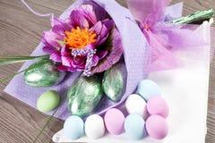 Bunte Ostereier mit Blumen und Schokoladeneiern Stockbilder