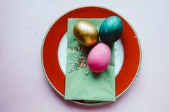Bunte Ostereier mit den Süßigkeiten, die auf Platte besprühen Lizenzfreie Stockfotos