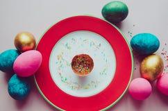 Bunte Ostereier mit den Süßigkeiten, die auf Platte besprühen Stockbilder