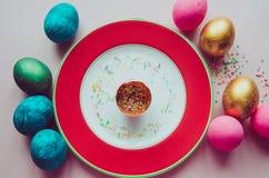 Bunte Ostereier mit den Süßigkeiten, die auf Platte besprühen Lizenzfreie Stockfotografie