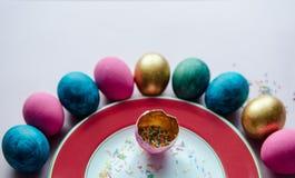 Bunte Ostereier mit den Süßigkeiten, die auf Platte besprühen Lizenzfreie Stockbilder