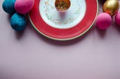 Bunte Ostereier mit den Süßigkeiten, die auf Platte besprühen Stockbild