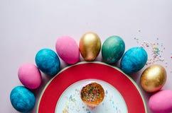 Bunte Ostereier mit den Süßigkeiten, die auf Platte besprühen Lizenzfreies Stockbild