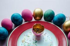 Bunte Ostereier mit den Süßigkeiten, die auf Platte besprühen Stockfotografie