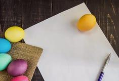 Bunte Ostereier mit leerem Papier und Stift auf Holztisch Stockfotos