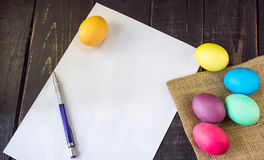 Bunte Ostereier mit leerem Papier und Stift auf rustikalem hölzernem t Stockfotos