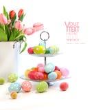 Bunte Ostereier mit rosafarbenen Tulpen auf Weiß Stockfotografie
