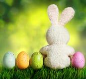 Bunte Ostereier und Kaninchen auf grünem Gras Stockbilder