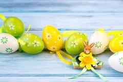Bunte Ostereier und Kaninchenstatuette auf einem hölzernen Hintergrund Stockfotografie