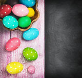 Bunte Ostereier und Tischbesteck auf einem schwarzen Hintergrund Lizenzfreie Stockfotos