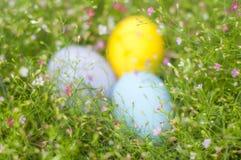 Bunte Ostereigrenze durch Blumenstrauß Hintergrund Stockbild