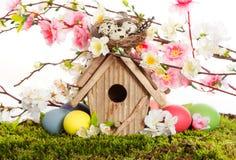 Bunte Ostern-Dekoration mit Vogelhaus und Eiern Stockfotos