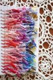 Bunte Palette des Threads für Kreuzstich auf einer weißen gewirkten Serviette stockfotos