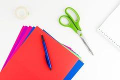 Bunte Papierblätter, Stift, große Scheren, Notizbuch und Band Lizenzfreie Stockfotos