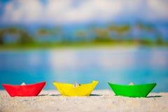 Bunte Papierboote auf tropischem weißem Strand Lizenzfreies Stockfoto