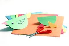 Bunte Papiere, Scheren und ein Papiervogel Lizenzfreie Stockfotos