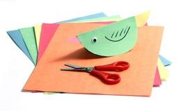 Bunte Papiere, Scheren und ein Papiervogel Stockbilder