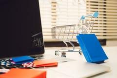 Bunte Papiereinkaufstasche in der Laufkatze auf Laptop Stockfotografie