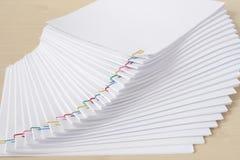 Bunte Papierklammer mit Stapel der weißen Schreibarbeit und der Berichte der Überlastung Stockfoto