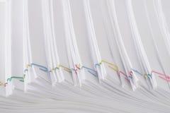 Bunte Papierklammer mit Stapel der weißen Schreibarbeit und der Berichte der Überlastung Lizenzfreies Stockbild