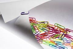 Bunte Papierklammern auf einem Papier Stockbild