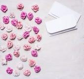 Bunte Papierrosen mit Umschlägen, Valentinstaggrenze, mit Draufsichtabschluß des Hintergrundes des Textbereichs weißem hölzernem  Lizenzfreie Stockfotografie