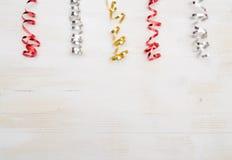 Bunte Papierschlangen auf weißem hölzernem Hintergrund Lizenzfreies Stockbild