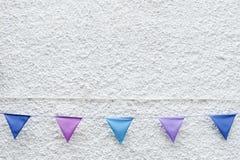 Bunte Partei kennzeichnet die Flagge, die am weißen Wandhintergrund hängt Minimales Hippie-Artdesign lizenzfreie stockfotos