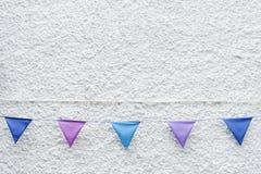 Bunte Partei kennzeichnet die Flagge, die am weißen Wandhintergrund hängt Minimales Hippie-Artdesign lizenzfreie stockfotografie
