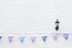Bunte Partei kennzeichnet die Flagge, die am weißen Wandhintergrund mit Wandlampenlicht hängt Minimales Hippie-Artdesign lizenzfreies stockbild