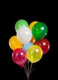 Bunte Partyballone auf schwarzem Hintergrund Stockfotos