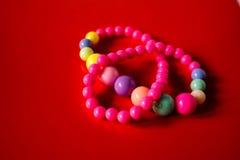 Bunte Perlen auf einem roten Hintergrund lizenzfreie stockfotos