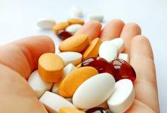 Bunte pharmazeutische Medizinpillen, -tabletten und -kapseln in der Hand auf weißem Hintergrund stockfotos