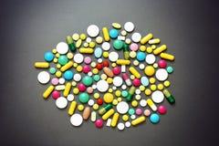 Bunte Pillen auf grauem Hintergrund Stockfoto