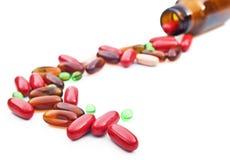 Bunte Pillen breiteten vor einer Pilleflasche aus. Lizenzfreie Stockfotografie